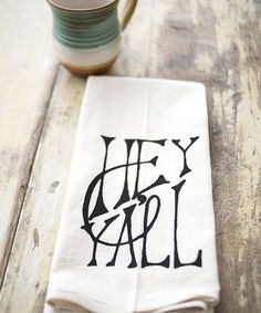 Wiping up spills and drying hands is more fun with this charming towel that features a friendly saying. Crafted from a cotton flour sack, it's an eco-friendly piece that brings function and style to the kitchen.