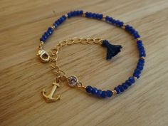 Sapphire beaded bracelet with gold plated anchor charm, CZ stone and a tiny tassel.. Bracelet size: 15.5 cm - 19 cm