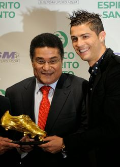 """(FILES) A file picture taken on November 4, 2011 shows Real Madrid's Portuguese forward Cristiano Ronaldo receiving the """"Golden Boot 2011"""" award, presented to Europe's best goal scorer, from former Portuguese football legend Eusebio da Silva Ferreira (C), in Madrid. Eusebio, who was the 1965 European Footballer of the Year and considered one of the best footballers of all time and best ever from Portugal."""