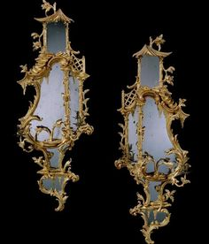 A fine pair of mid 18th century Chippendale period carved giltwood girandoles with 18th century replaced plates within divided asymmetric cartouche shaped frames with pagoda roofed crestings, foliate branches and lattice fence, the sides each with profuse scroll and foliate carving, with scrolling foliate branches with brass nozzles and pans above a foliate pierced and mirrored pendant apron.English, circa 1765.Price range: £100,000