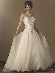 Decorated Basque Waist Signature Wedding Gown This exquisite designer bridal dress features a dramatically embroidered and crystal beaded sweetheart bodice with corset closure. A Basque waistline sits