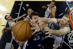 Memphis Grizzlies Marc Gasol, center, is defended by, from left to right, San Antonio Spurs Manu Ginobili, Tim Duncan, Kawhi Leonard and Matt Bonner during the first half in Game 1 of a Western Conference Finals NBA basketball playoff series on Sunday, May 19, 2013, in San Antonio. (AP Photo/Eric Gay)