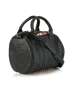 Alexander Wang Rockie Textured Leather Duffle Bag - Black Deserving of its cult following, Alexander Wang's 'Rockie' duffle is beautifully soft and supple in black textured lamb leather and features four clear-cut rows of rose gold studs to the base. The label's signature dog clips complete the grunge-cool design, while hidden exterior pockets provide safe storage for your phone and keys. Rockie Textured Leather Duffle Bag by Alexander WangDimensions: Height 21cm x Width 22cm x Depth…