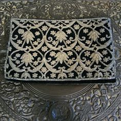 This velvet clutch from the 1960s features a black velveteen body and gold embroidery allover front and back. Fully lined in black faille with multi-compartment interior. Snap closure