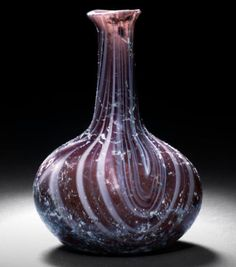 A Roman aubergine marbled glass flask  Circa 1st Century A.D. Decorated with opaque white trails in the glass appearing pink in places, the small flaring mouth with cut-off rim, the tall neck expanding towards the flattened spherical body, 3in (7.7cm) high