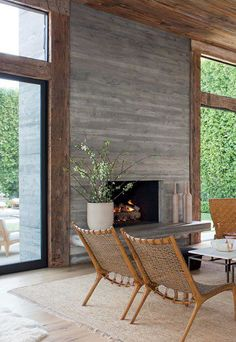 Board-formed concrete fireplace framed by reclaimed oak beams: