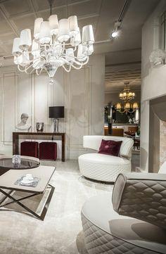 amenagement salon très luxueux, grand luminaire baroque aux multiples mini luminaires avec des abat jours blancs, table carrée et ronde, grande cheminée en gris et blanc, fauteuils semi ronds en gris pastel et blanc design futuristique