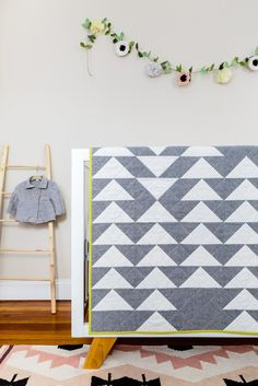 Tiny little plus signs dot the white triangles that are the scene stealer of this pretty, modern baby quilt. The quilt top's subdued palette contrasts beautifully with the rich, saturated red-and-cora