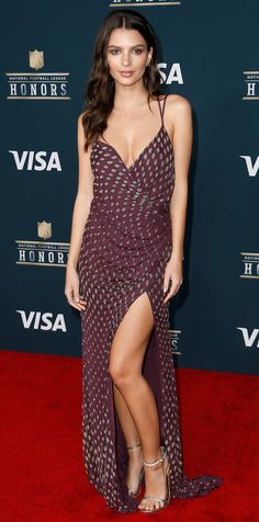 Emily Ratajkowski brought her supermodel smolder to the NFL Honors red carpet in a bejeweled burgundy Kayat gown featuring a draped bodice and a racy high slit.
