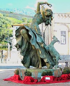 This is a statue of Gina Lollobrigida. Gina Lollobrigida played Esmeralda in the 1956 French film adaption, Notre Dame de Paris. This statue is in Italy, Pietrasanta Natale. It has some gold elements. It fearures her in mid dance with flowing skirt and Djali standing on two legs.