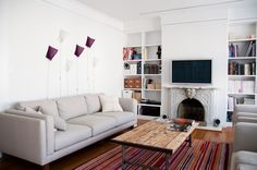 love the light gray couch with white walls and a pop of purple