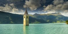 Lake Resia, The Sunken Town Where You'll Walk On Water  In Italy's Lake Resia, near the borders of Austria and Switzerland, a lone bell tower shoots up from the perfect, blue-green water. It's the only visible remnant of Graun...