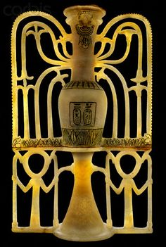 Unguent vase from the tomb of Tutankhamun. Elongated vase flanked with floral openwork ornamentation, cut from a single block of alabaster. On the neck of vase is the head of Hathor, on the bowl are two beasts pertaining to the god, and the rectangle below contains the protocol of the king. The ornamental stand is flanked with ankhs