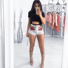 Black crop top, fishnets, high waisted shorts w/ flowers, clear boots or heels