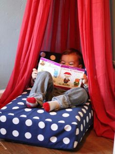 Hoola hoop draped on fabric over a crib mayoress set on the floor creates a cute little reading nook :) too cute!!
