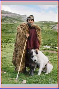 Portrait of shepherd wearing sheepskin cloak, wearing green hat, holding stick standing with sheepdog against background of Urdele Pass, Carpathian Mountains, July Historical Clothing, Historical Photos, Empire Ottoman, Carpathian Mountains, Green Hats, Folk Costume, People Of The World, Eastern Europe, Traditional Outfits