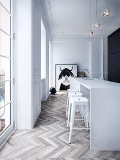 chevron wood flooring + white walls + waterfall countertop + white metal stools + black wall + graphic art
