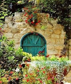 A round turquoise door in a rock wall- rustic beauty!