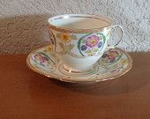 Queen Anne bone china tea cup and saucer. Multicolor floral with gold design. Scalloped edge footed tea cup. $20.00, via Etsy.