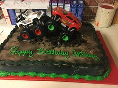 """1/2 sheet monster truck cake. Iced in brown icing and airbrushed with brown and black tones. The """"dirt"""" is crumbled chocolate cake. The trucks are toy trucks."""