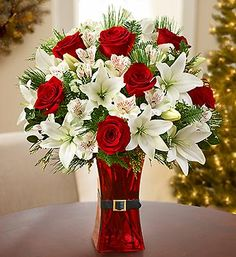 Red and white Christmas flowers featuring red roses and white lilies in a red vase with a Santa belt make the perfect Christmas floral arrangement!