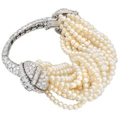 Cartier Vintage Natural Pearl & Diamond Bracelet    Vintage natural pearl and diamond bracelet, composed of a torsade of natural pearls strung on hand-knotted silk, attached to a an ornate diamond-set, partway bangle, mounted in platinum and set with approximately 16.00 total carats of circular-cut and baguette-cut diamonds, signed Cartier.