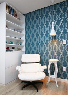 Para valorizar o canto da leitura e a poltrona, Gláucio sugeriu um papel de parede azul petróleo com estampas discretas. Os demais móveis, como a poltrona e a estante, foram escolhidos na cor branca.