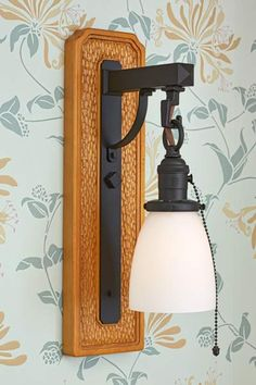 A white shade softens the look of wood and iron. The Craftsman-style wallpaper was inspired by a traditional William Morris design