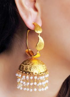 This pair of spectacular gilded earrings by Urban Dhani is perfect to enhance the look of your traditional wear. The earrings have a hoop as a top with leaf design engraved on it. Wear it in style to flaunt the ravishing golden jhumkas, complete with engravings and pearl hangings.