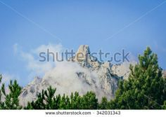 top of mountain against blue sky in clouds