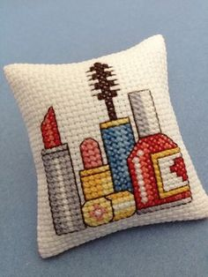 """cross stitch pincushion makeup This unique pincushion features cross-stitched makeup (lipstick, mascara, and nail polish). It was completely hand-stitched. The reverse side has an image of cross-stitched lips. It is stuffed with new polyester fiberfill. Size: Approximately 2"""" x 2"""