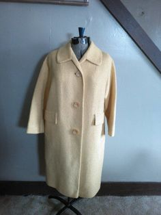 This cute coat has a Nubby wool texture and features a weave of dark & light yellow in color. There are button closures down the front & pockets on