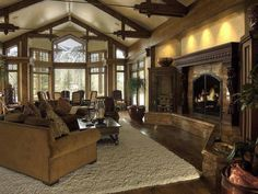 Traditional Great Room with Curved wood, Hardwood floors, stone fireplace, Exposed beam, High ceiling, Built-in bookshelf