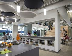 The Hulu office in Santa Monica has an open plan, circular acoustical clouds, polished concrete floors, open shelving, wood seating steps, unfinished ceilings and cylindrical pendant lighting.