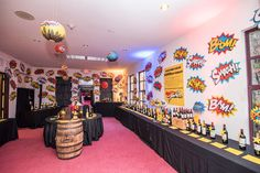 <p> Pop Art-style stickers of superhero phrases covered the walls in one of the silent auction rooms.</p>