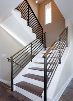 A simple and stylish way to make the staircase look simple yet chic and eye-catching is to use contrasts. In this case, for example, the wooden stairs sit on a crisp white background and the metal guardrail with wooden handrail frame them beautifully.: