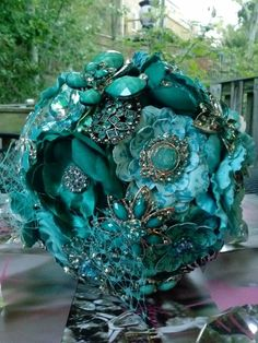 This Turquoise and Deep Sea Blue Brooch Bouquet is covered with silk and satin rosettes, acrylic and paper flowers. Adorned with sparkling brooches and Swarovski crystals, and Butterflies..