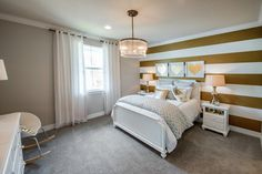 An accent wall in gold stripes makes this neutral girl's bedroom pop! | Pulte Homes