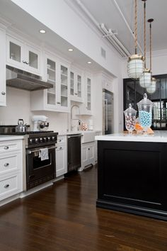 "So many details to love - white cabinets, dark floor, Viking appliances, farmhouse sink, ""feet"" on cabinet under sink, glass front upper cabinets, kettle, mixer, candy jars..."