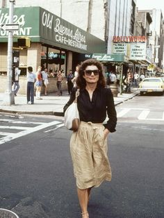 Jackie O wears a black button-down blouse, linen midi skirt, sandals, a shoudler bag, and rectangular sunglasses