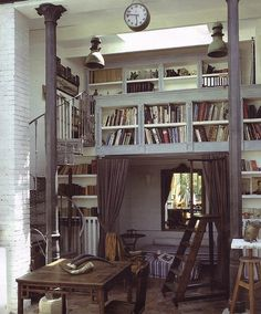 I love everything about this...circular stairs to the second level, two sided book cases over the entry way to the nook seating area in front of the window behind the curtain. Just beautiful.