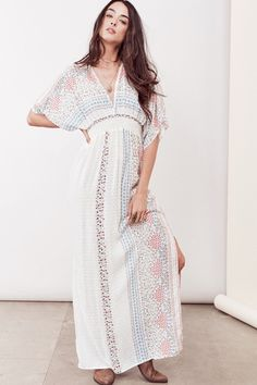 Effortlessly chic, double v-neck, border printed Swiss dot caftan maxi dress featuring side slits, smocked waist and tie neck detail.100%Rayon Model is 5'10, wearing a S/M.