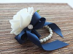 This elegant wrist corsage is made with real-touch white roses accented with rhinestone and navy ribbon, finished on pearl bracelet. with purple ribbon tho. Homecoming Flowers, Homecoming Corsage, Prom Flowers, Silk Flowers, Wedding Flowers, Flower Bouquets, White Boutonniere, Corsage And Boutonniere, Boutonnieres