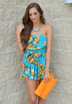 This strapless blue & mint green romper with yellow & orange floral printed design is perfect paired with a neon clutch for a night out on the beach!