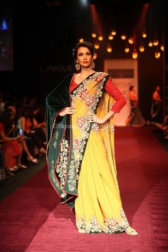 an auric yellow silk georgette saree with bold velvet applique in scarlet red and fern green combined with a metalic zardozi border; and a red raw silk blouse detailed with tone on tone thread embroidery on the sleeves, teamed with a green velvet embellished sash.