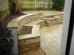 Natural stone retaining wall with bench and raised planters in Indian stone and Purbeck