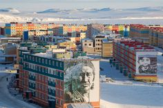Brightly coloured apartment blocks with murals of native Chukchi in the town of Anadyr. Chukotka, Siberia, Russia