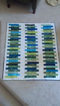 """""""Stratified Sample"""". Lots of feather quilting practice on this jelly roll quilt."""