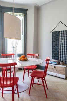 Love these red Salt Chairs from DWR mixed with the white table.