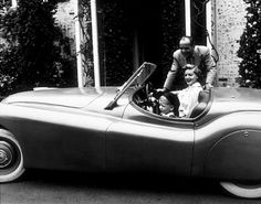 Humphrey Bogart, Lauren Bacall, and their son, Stephen, in his Jaguar XK120 at home in Los Angeles, CA, 1952.